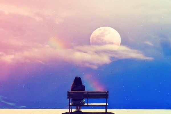lady reflecting on bech, looking at moon and rainbow