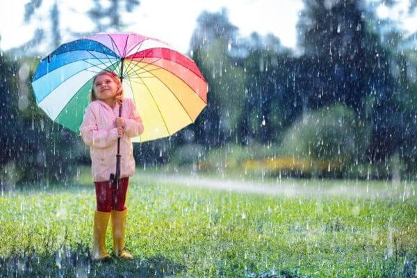 child playing with umbrella raining