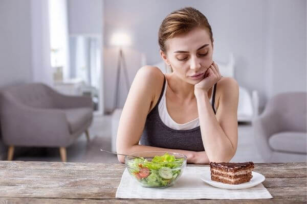 Lady looking at choice of salad or cake