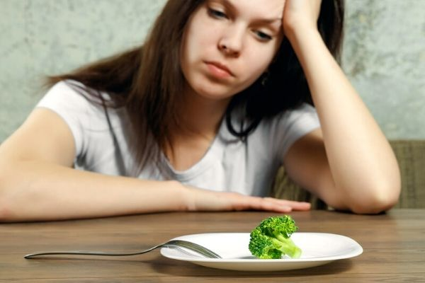 lady looking bored at one piece of broccoli on plate