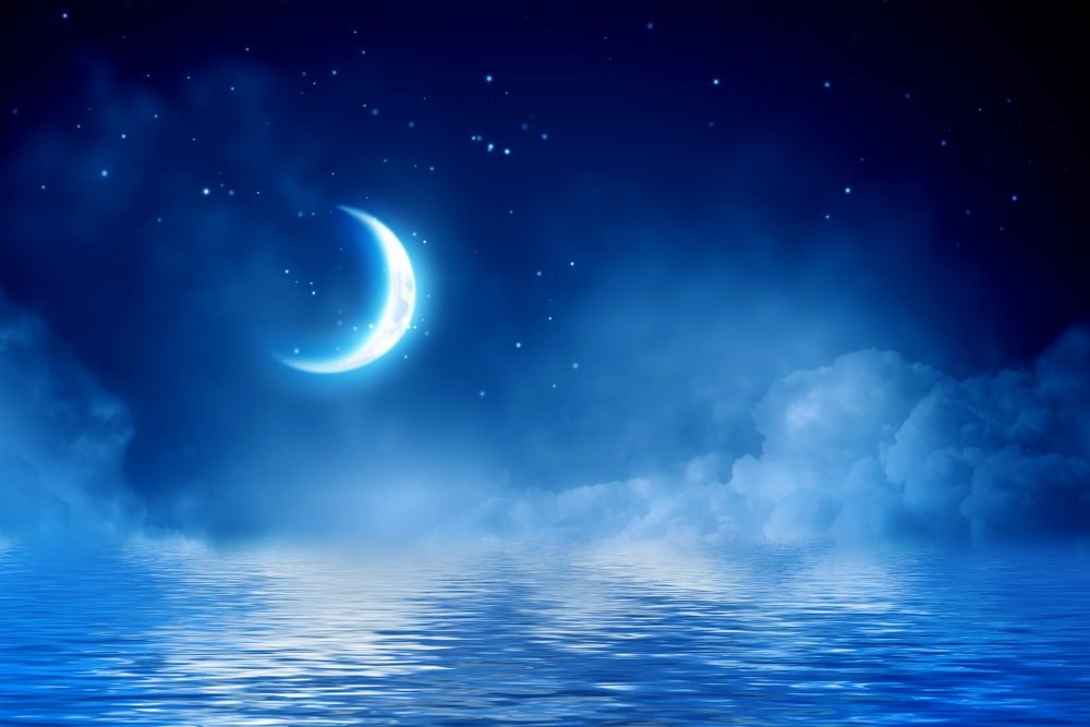 half moon above water at night