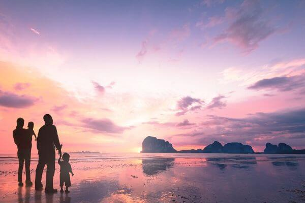 Family of 4 looking at sunset in beach
